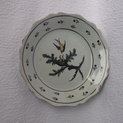 Assiette ancienne en faïence de Nevers à décor d'un oiseau venant nourrir ses petits dans le nid